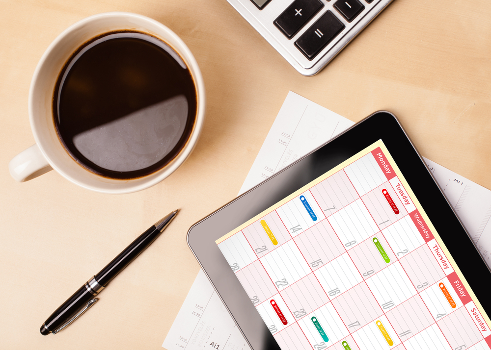 Workplace with tablet pc showing calendar and a cup of coffee on a wooden work table close-up-1